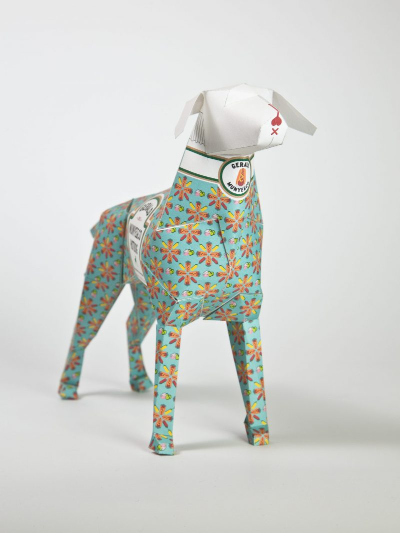 Paper dog model with a mint green background with orange flowers over the top of it