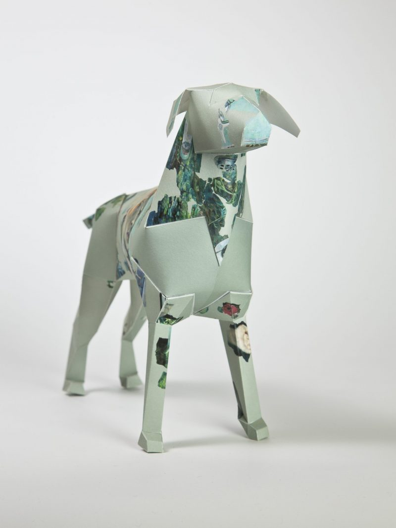 A paper dog model sculpture in a 3D form. The design is a light green with darker green patches.