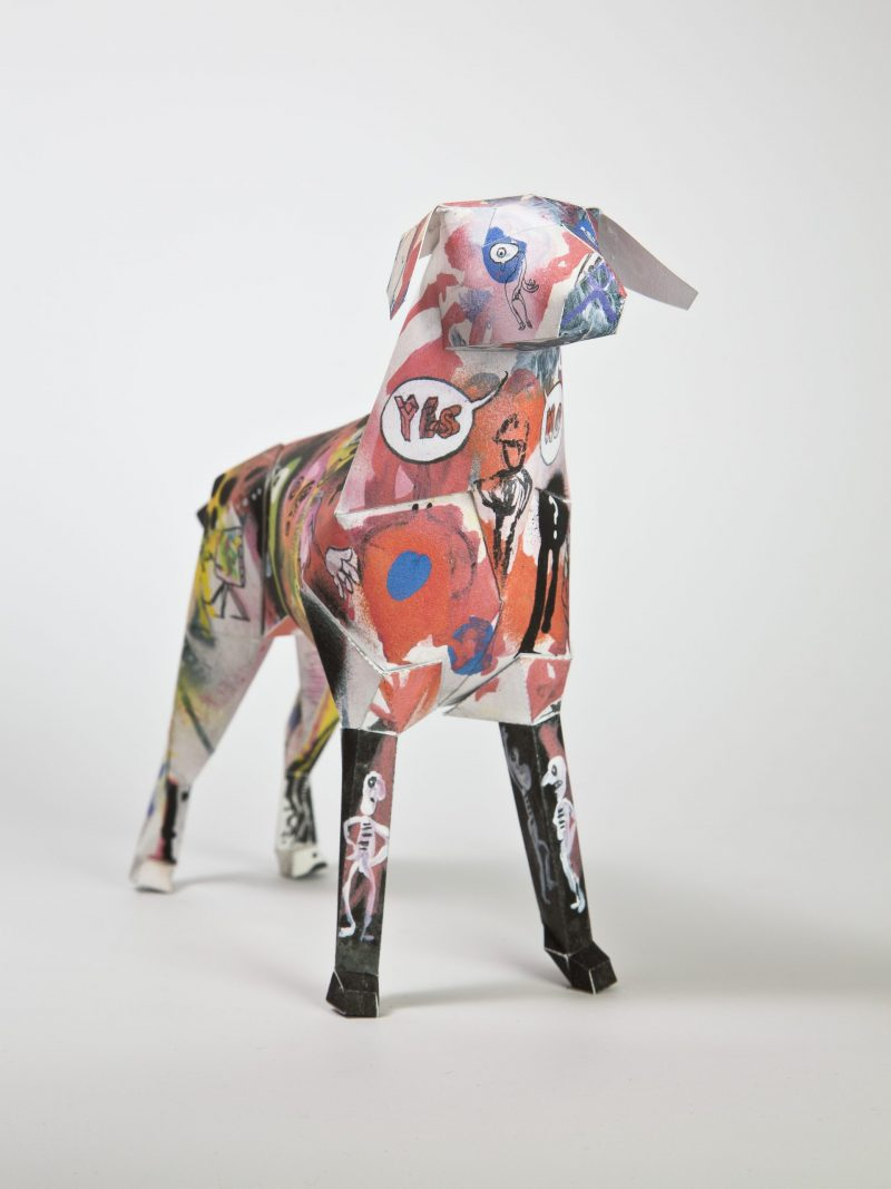 3D paper dog model with a graffiti spray style pattern all over it.