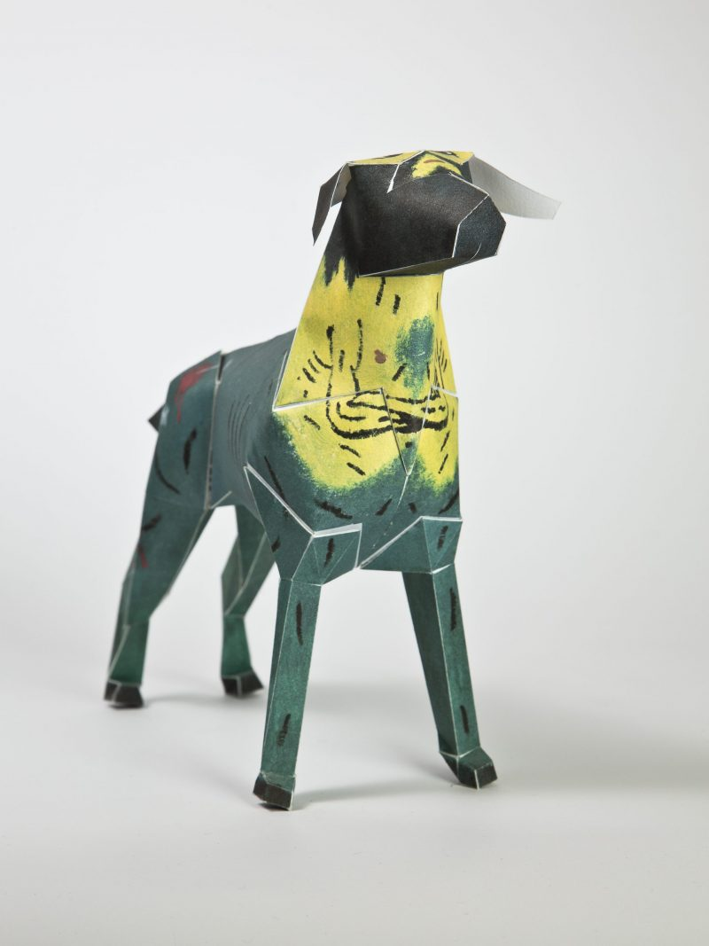 A blue/green paper dog sculpture with a yellow neck