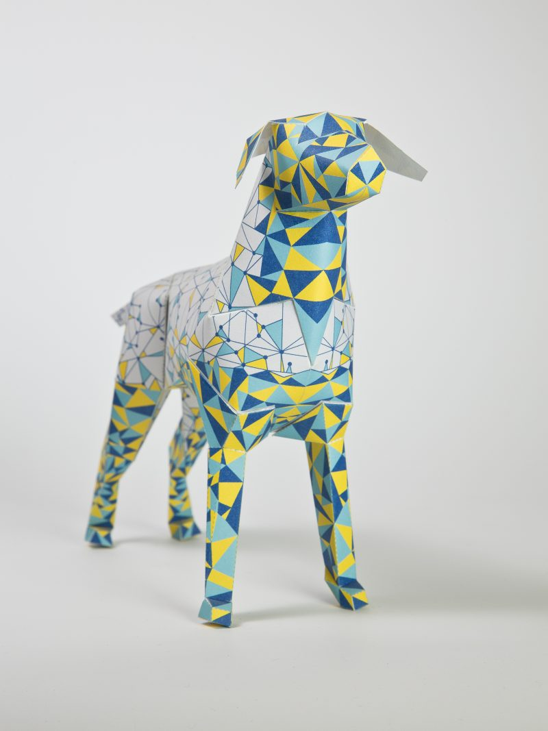 A white paper dog model in 3D sculpture form with lines on it connecting to form traingles all over the body. On the face and legs the traingles are filled with colour- yellows and blues. Part of an international design exhibition by design leaders Lazerian whereas artists and designers were invited to customise the dog sculpture (which is Lazerians mascot) in their own unique style. The designer of this dog were eskimo Creative who are from manchester.