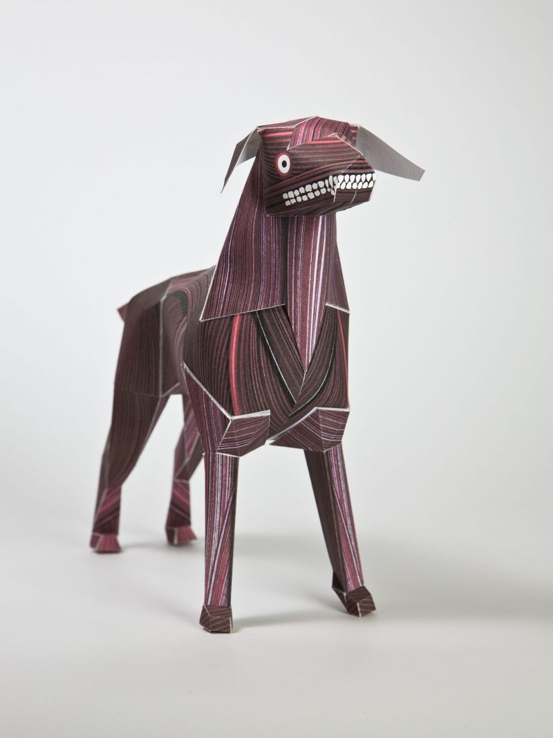 A 3D model of a red paper dog sculpture. It has a mencaing grin showing teeth and a googly eye. The design also shows a wood veneer type of look with lines being drawn on the model.