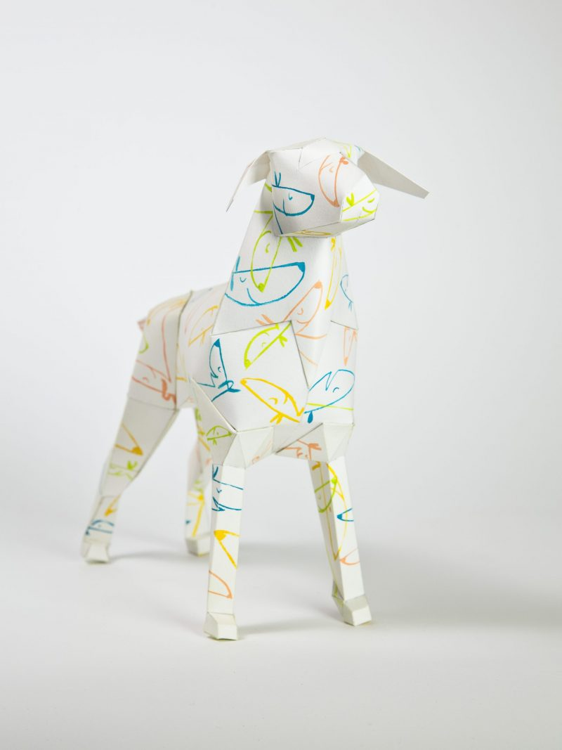 A image of a 3D paper dog sculpture with a pattern of line drawings of dogs faces in yellow, orange and blue.