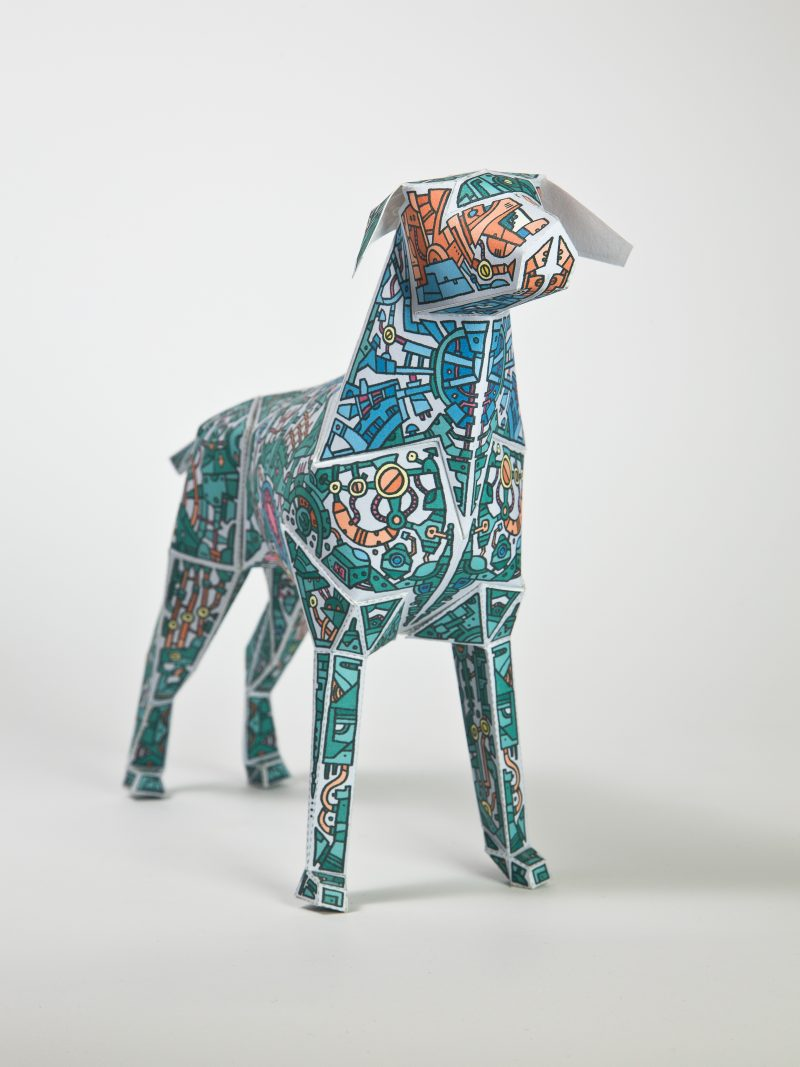 Main view of a green paper dog model with doddles of mechnical drawings all over them. Designed by Barney Ibbotson for an international exhibition by design studio Lazerian
