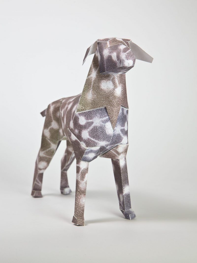 A 3D model of a paper dog with a brown design with white circles and white lines attaching them together