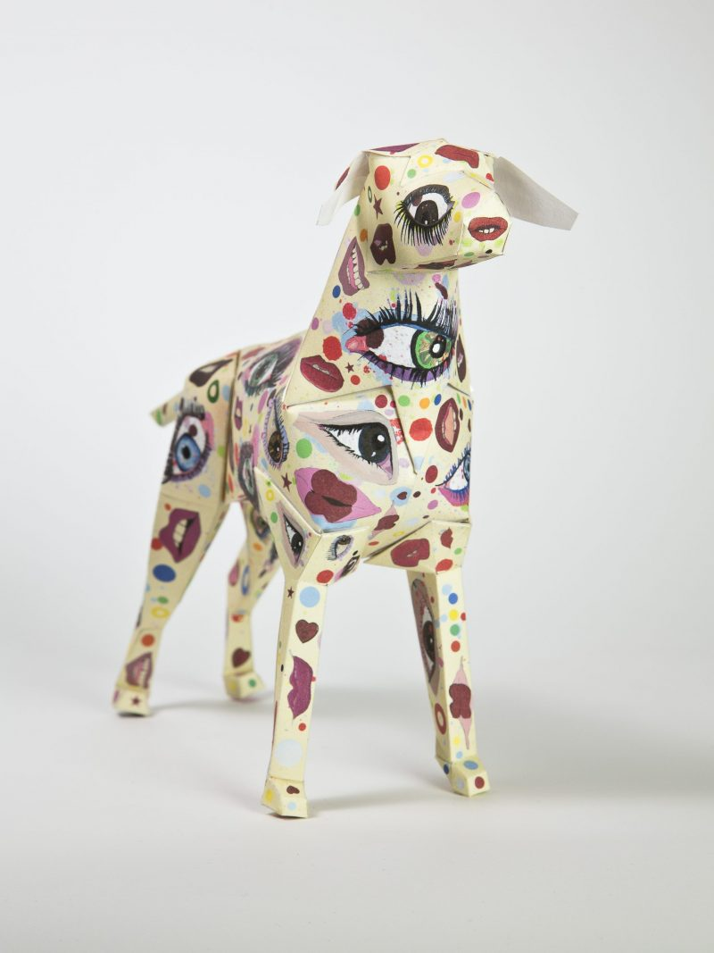 3D model of a paper dog with lips and eye design all over it. The colours are mainly pinks, reds, yellows, greens and purple.