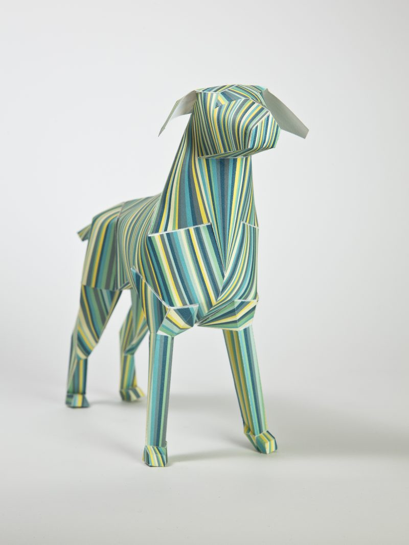 A paper dog model in a 3D sculpture form. The pattern consists of vertical lines in a varity of shades of greens, yellows and greys. PArt of a exhibition by design studio lazerian.