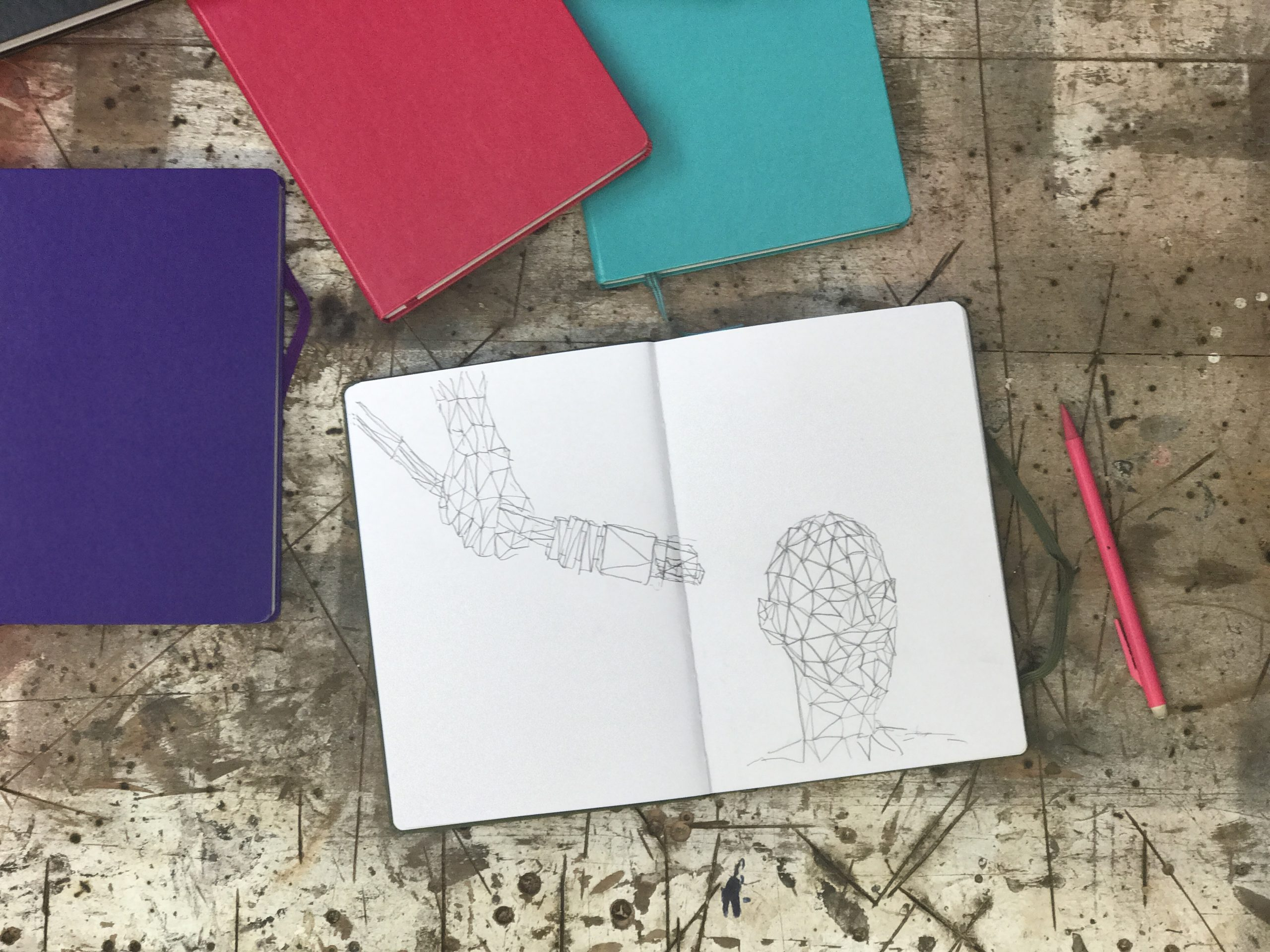 4 notes books on a table with a pencil nect to 1 open one. The other 3 are behind the open one and are purple, pink and blue. On the open paged notebook there is a artistic sketch design of a head with a plug being attached to the back of the head.