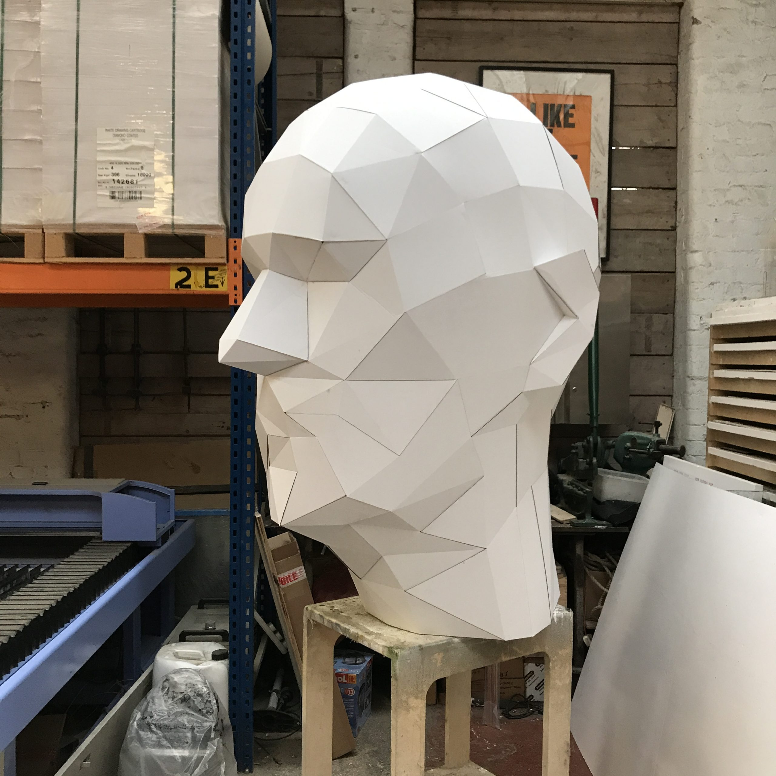 Large 3D paper head model in a workshop