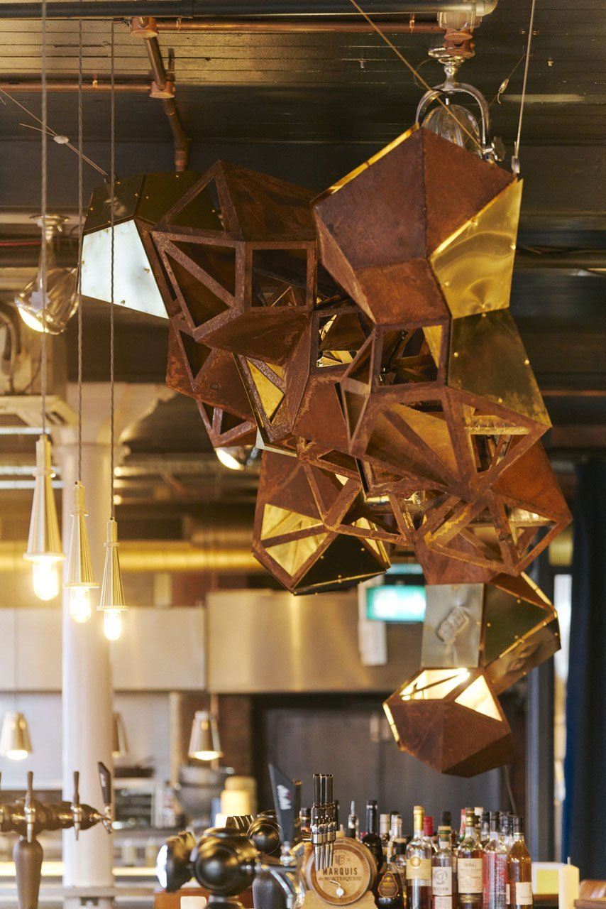 Steel sculpture with a rusting effect hung over a bar based in Manchesters Northern Quarter- Cottonopolis. It shows the art sculpture from a side view as you enter the building. Some of the structure has triangular parts cut out of it where the other parts have a full rusty corten steel piece placed over the triangular shapes. It is a 3D model.