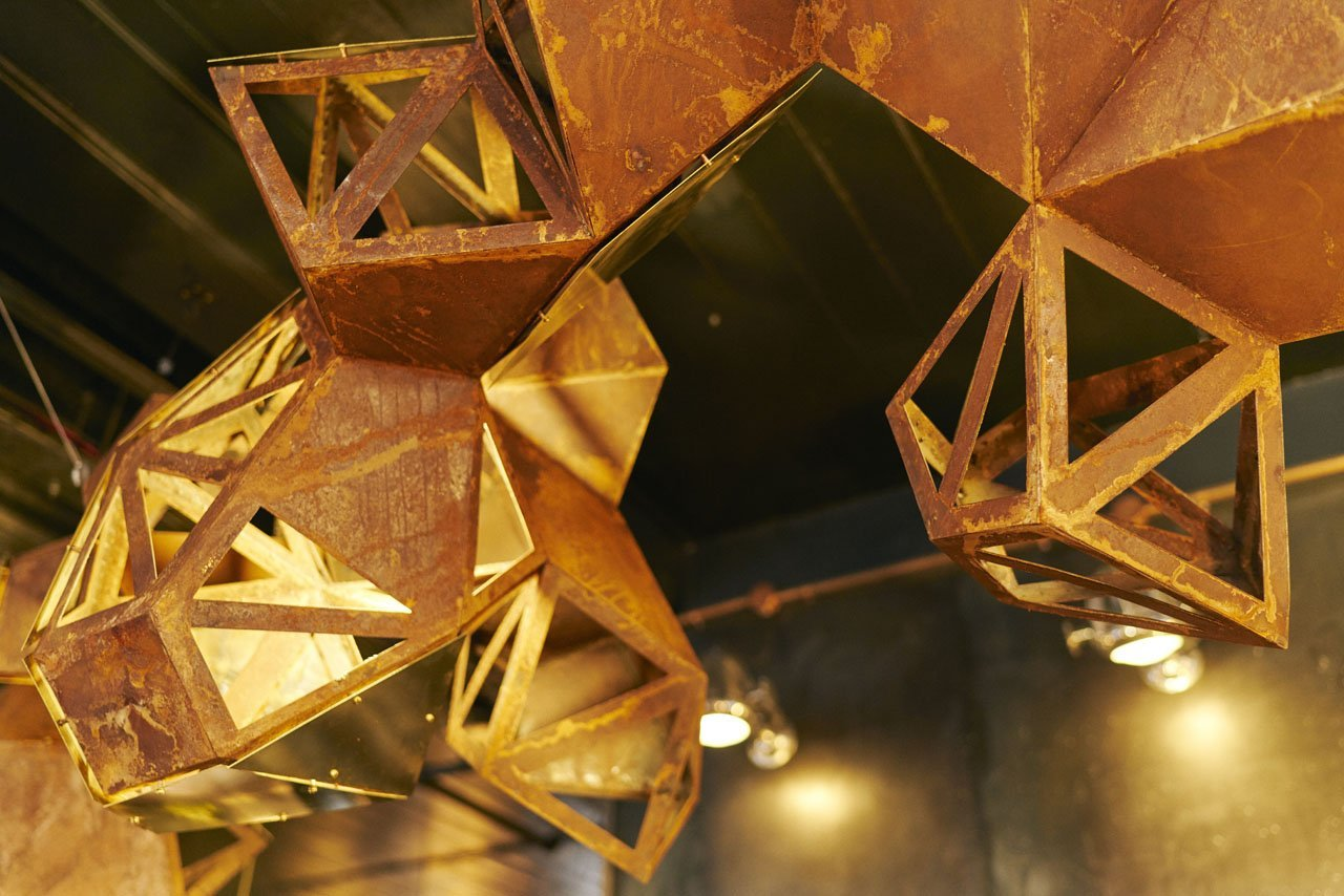 Steel sculpture with a rusting effect hung over a bar based in Manchesters Northern Quarter- Cottonopolis. It show around 1/3 of the sculpture from a angle where you are looking at it from standing underneath it. Some of the structure has triangular parts cut out of it where the other parts have a full rusty corten steel piece placed over the triangular shapes. It is a 3D model.