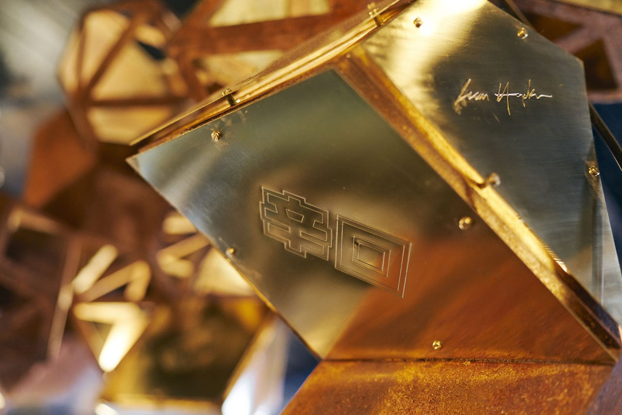 Steel sculpture with a rusting effect hung over a bar based in Manchesters Northern Quarter- Cottonopolis. It show a close up of the sculpture. The parts have a full rusty corten steel piece placed over the triangular shapes with laser engraved Japanese patterns on them. It is a 3D model.