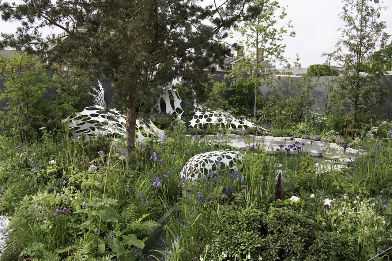 SIde view of the Manchester Garden at the 2019 RHS Chelsea flower show showcasing the white carbon fibre design exterior sculpture by Lazerian
