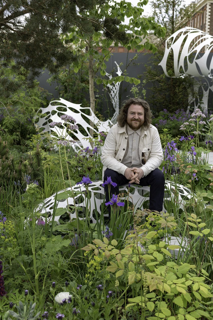 Liam Hopkins of Lazerian sitting on his art sculpture in the Manchester Garden at the 2019 RHS Chelsea Flower Show
