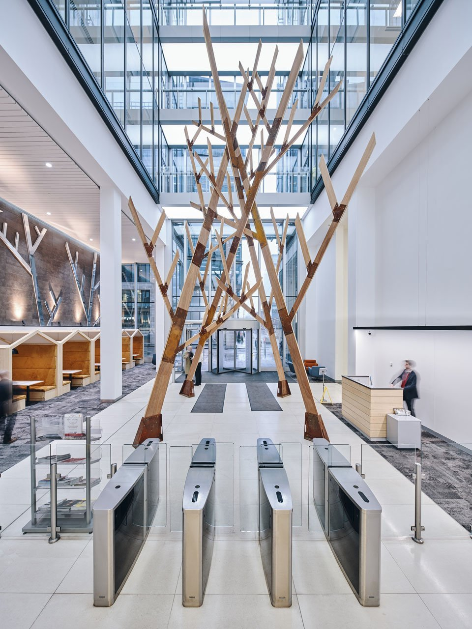 Full shot of a interior statement installation of a 40ft tall wooden contemporary style designed tree. It is in the foyer of a smart exclusive office building in business district Spinningfields in Manchester