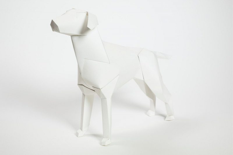 Left hand view of a paper white plain dog sculpture which is also the mascot and logo of leading known design studio Lazerian. The dog affectionately known as Gerald what the star of his own worldwide exhibition and design project.