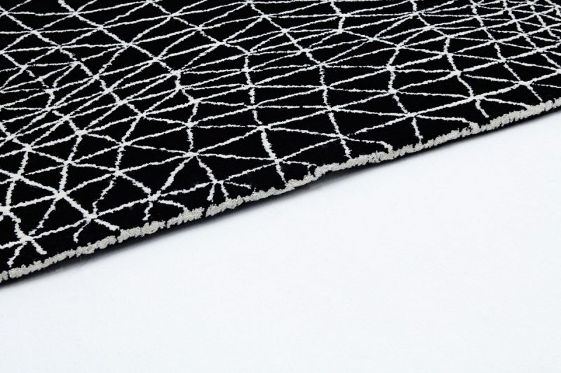 Extreme close up of the edge of a black rug with white lined design on it. Designed by Lazerian