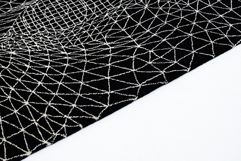 Edge of a black rug with white lined triangular shape on it. Designed and sold by Lazerian