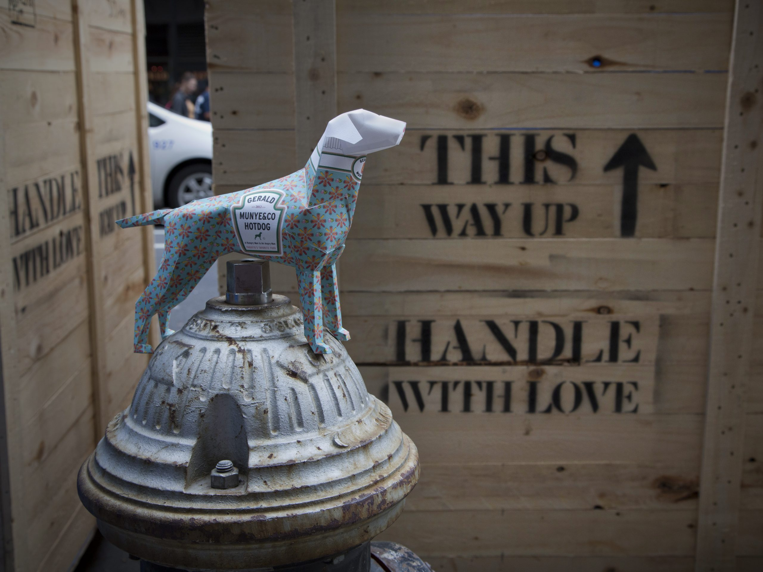 A 3D paper dog model sat on a New York water hydrant with wooden crate boxes in the background with 'This way Up and a upwards arrow sign. It also handle with care stenciled on the wooden box.