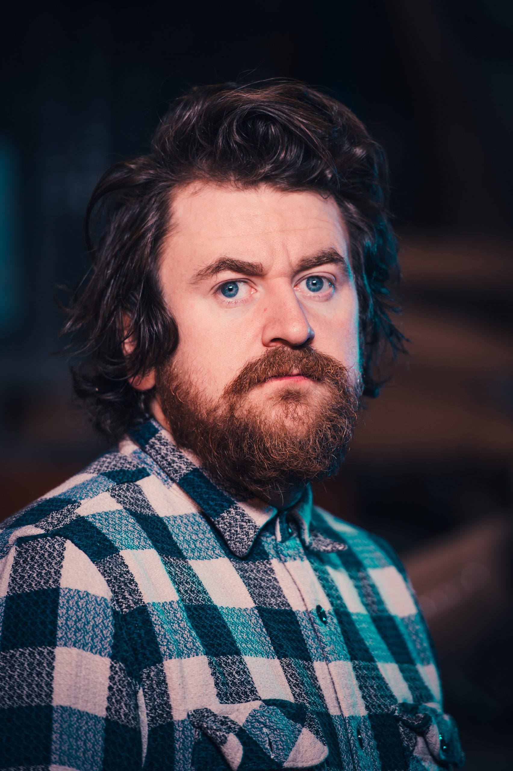 Portrait photo of a serious looking breaded man wearing a blue and white checked shirt. It is Liam Hopkins of Manchester design studio Lazerian