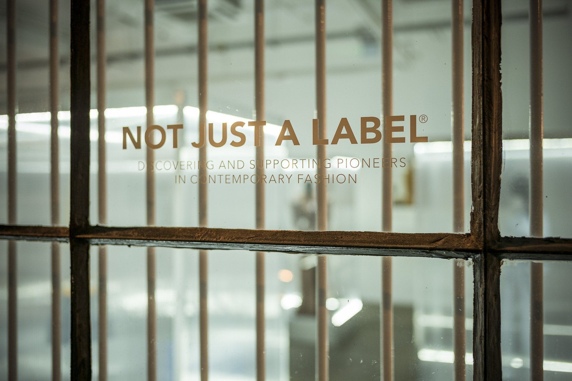 A window with vinyl lettering saying 'not just a label' and bars over the top of it
