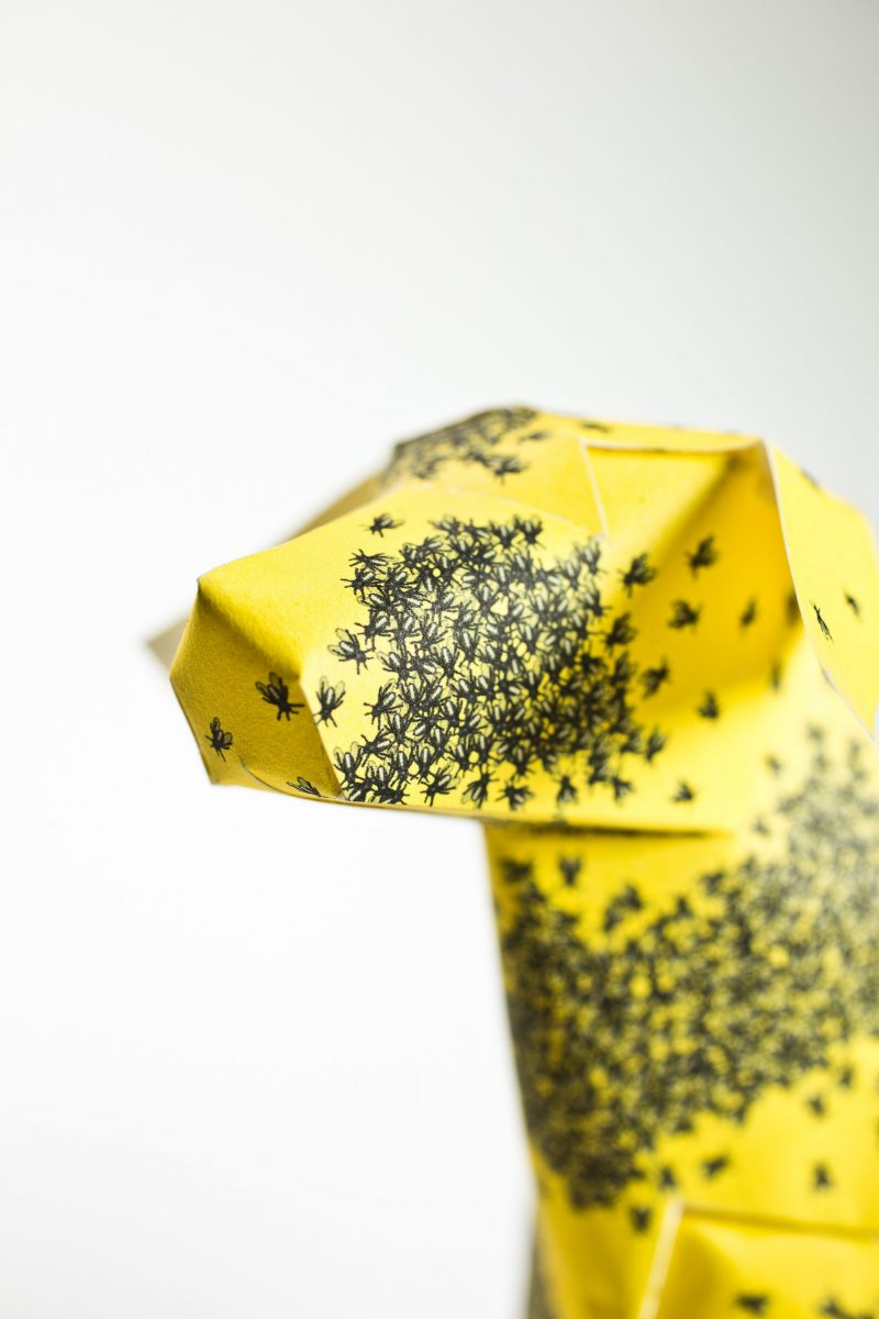 Close up of a yellow paper dog with bees on it