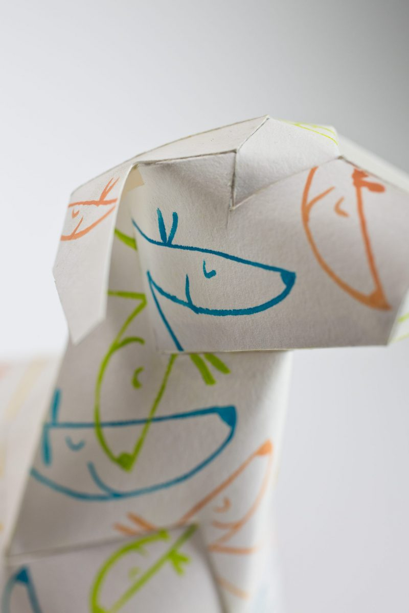 A close up view of a white 3D dog sculpture with blue, orange and green line drawings of dogs faces on the paper dogs face.
