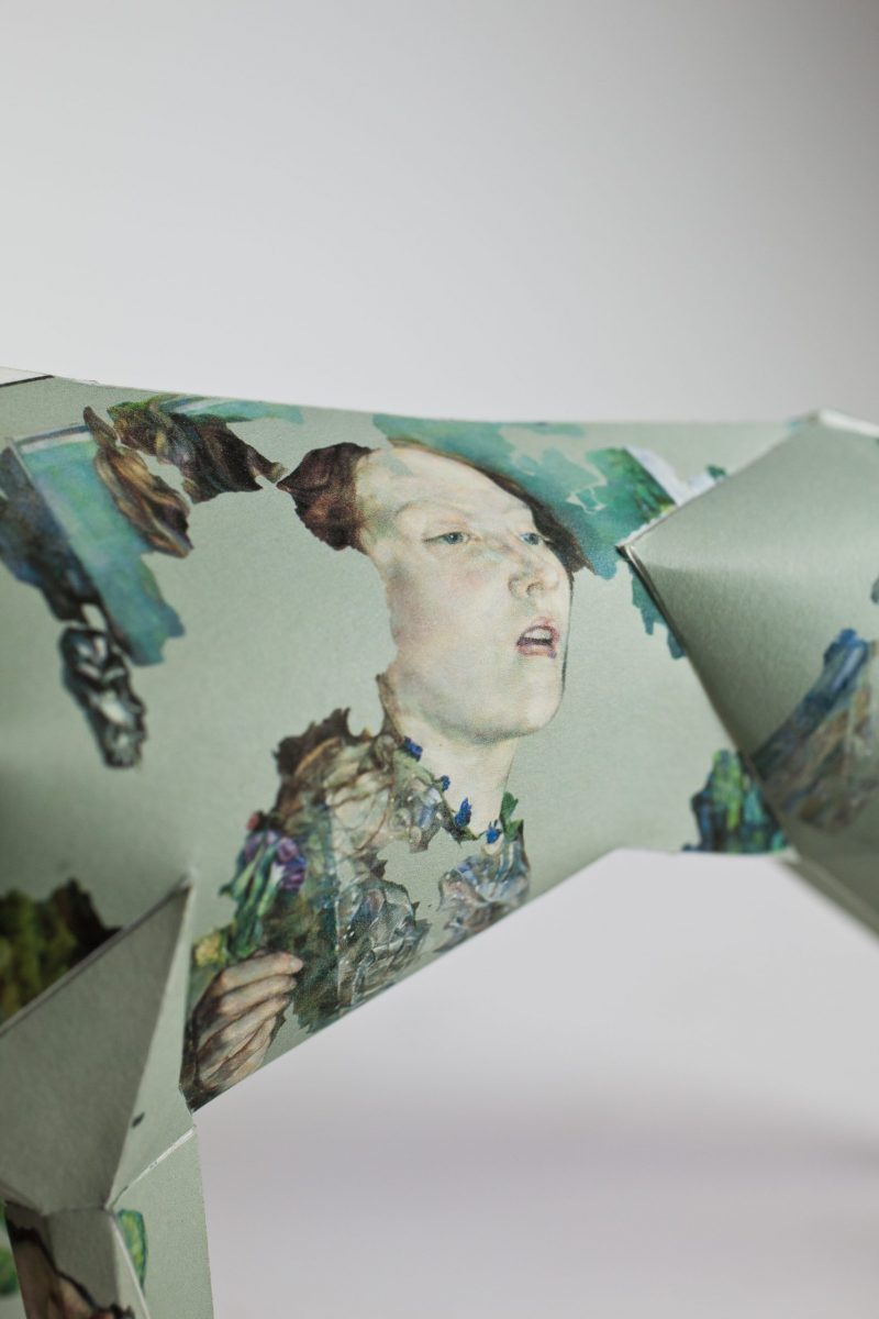 Close up version of a paper dog 3D model. The design it is showing is a abstract drawing of a lady on the torso of the paper dog.