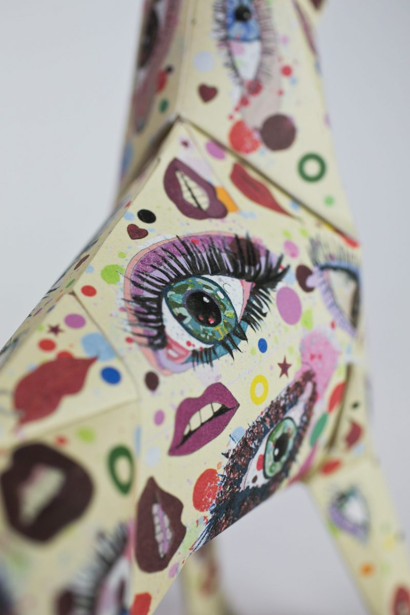 Close up of various eyes and lips as a pattern on paper. The eyes and lips are all different bright colours such as reds, pinks, greens and yellows