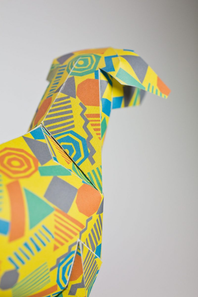 Close up of a yellow 3D paper dog model showing the head facing away from the camera. It has 80's style geometric shapes in oranges, purples and blues.