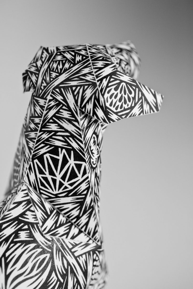 Close up of the head of a paper dog model. Covered in a monochrome pattern