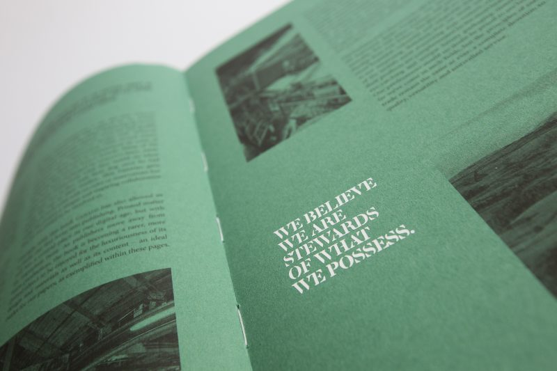An open book with green pages and black and white photographs and white text on it. The book is the design publication that accompanyies the international Gerald exhibition which focused on 101 artists and designers who put their own creative spin on the paper dog.