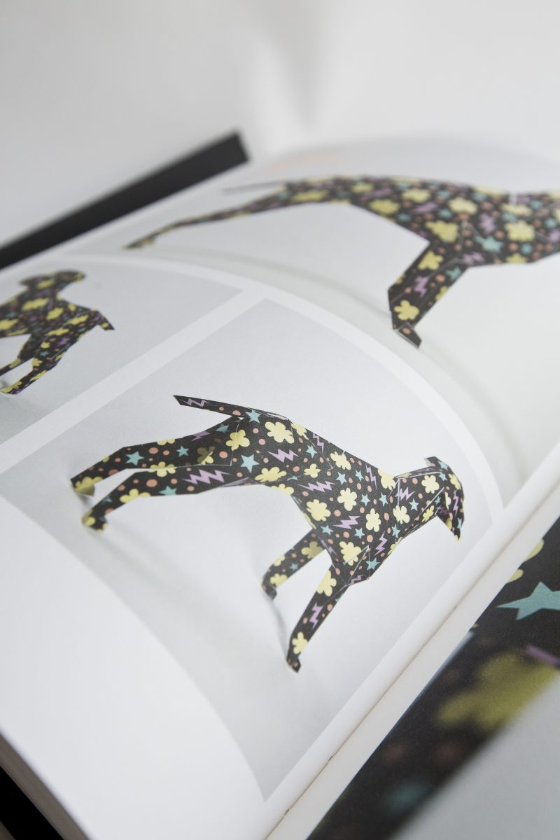 Focusing on a page from a open book. On the page is a black paper dog with blue stars, yellow cloud shapes and pink lighting bolts all over the dog. The book is the accompanying publication to the international design exhibition of Gerald the Lazerian dog.