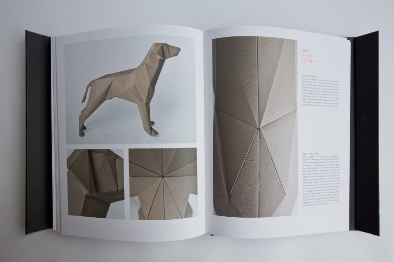 A open book showing 2 pages with a design of a brown paper dog and close up shots of it. the book is a design publication from Lazerian called Gerald and is the accompanying edition to the international exhibition which displayed over 101 paper dogs all of which are displayed in this book.