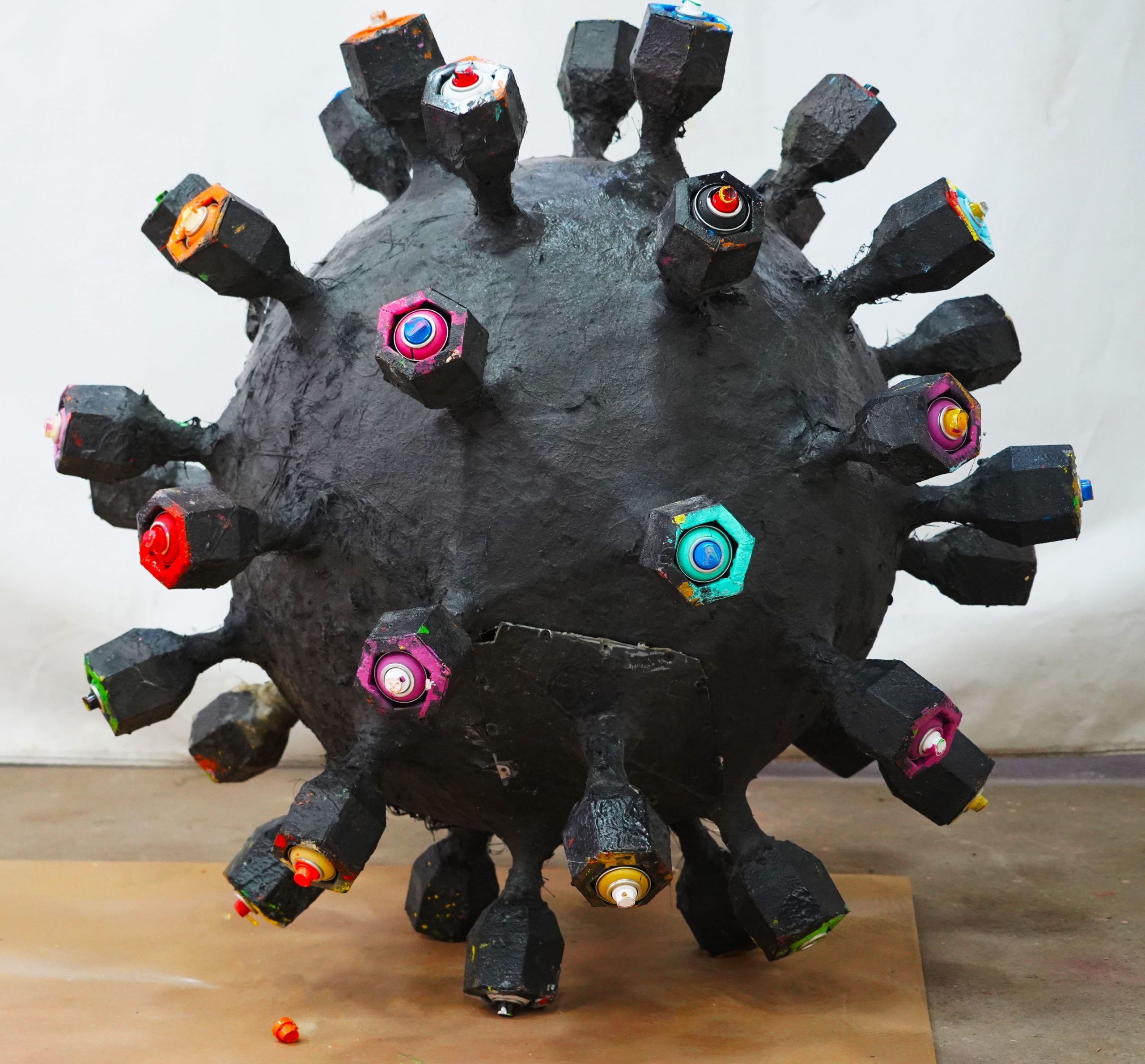 A close up of an corona inspired sculpture from art and design studio Lazerian. It is a large black ball with 'arms' sticking. It is the artists Liam Hopkins, interpretation of the corona virus in an visual form.