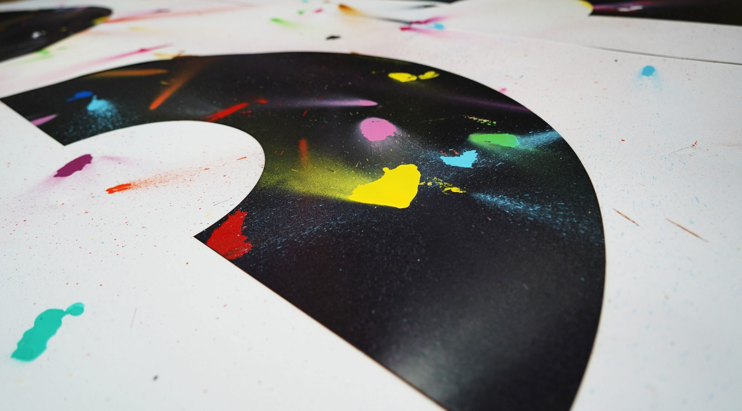 Artwork on white paper with a black crescent shape covered in colourful spray paint