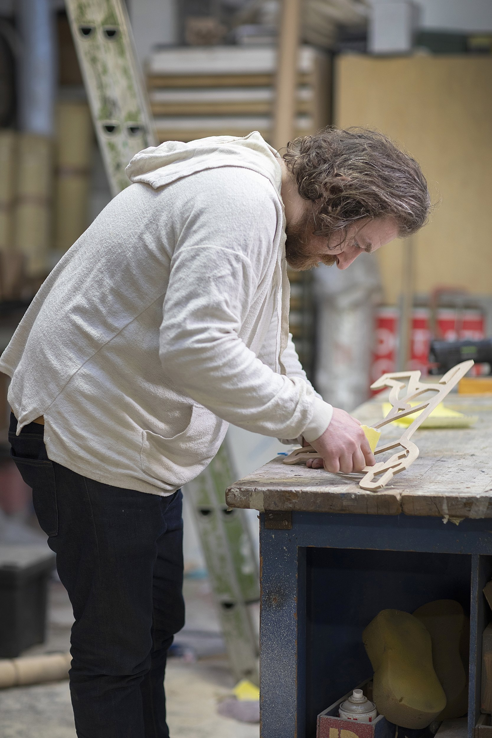 Liam Hopkins, owner and designer of design studio Lazerian at work. He is sanding his mascot Gerald that has been sculptured out of wood.