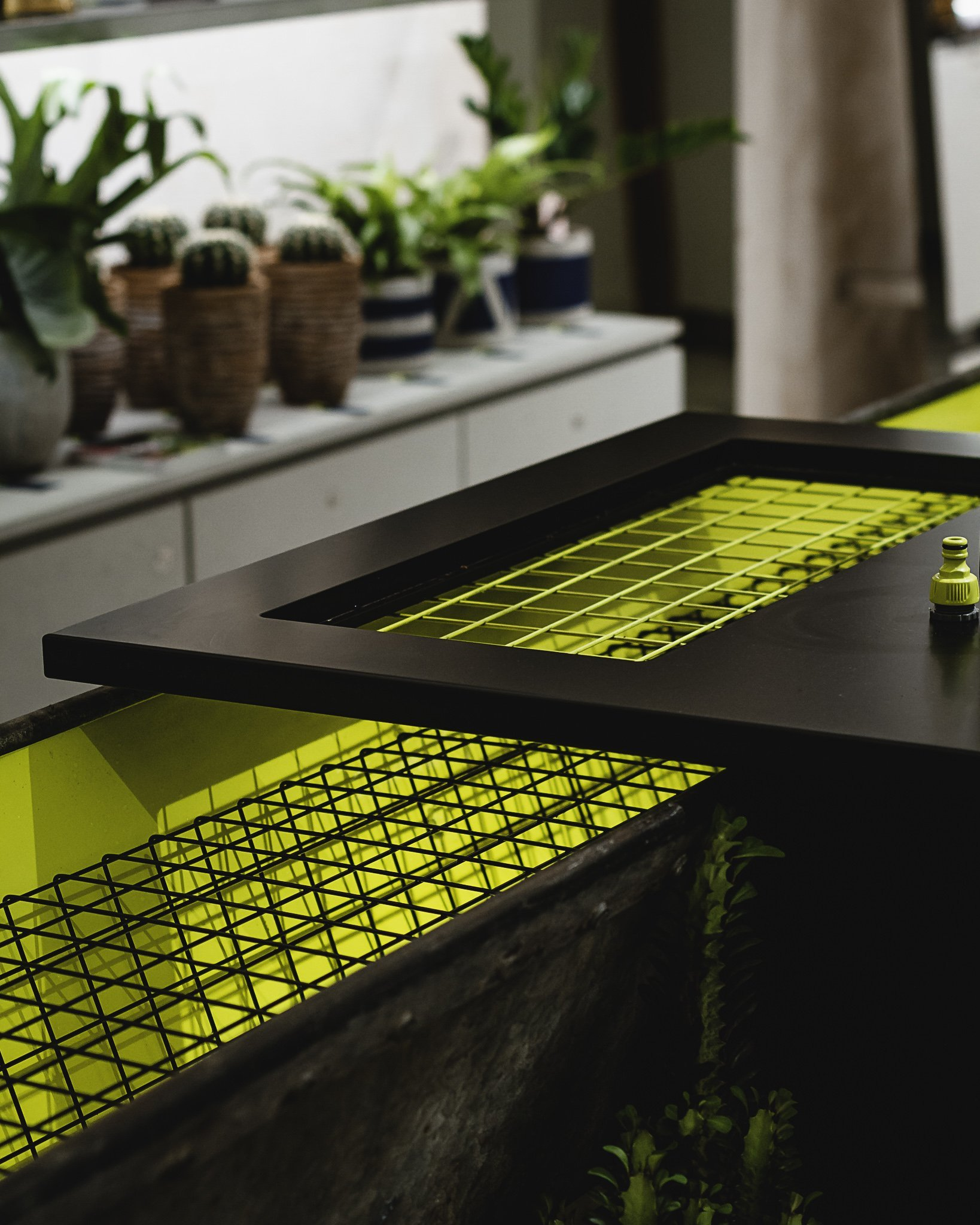Flourescent yellow inner with a black cage and cover on this sink for a shop interior fit out upcycled from a vintage horse trough