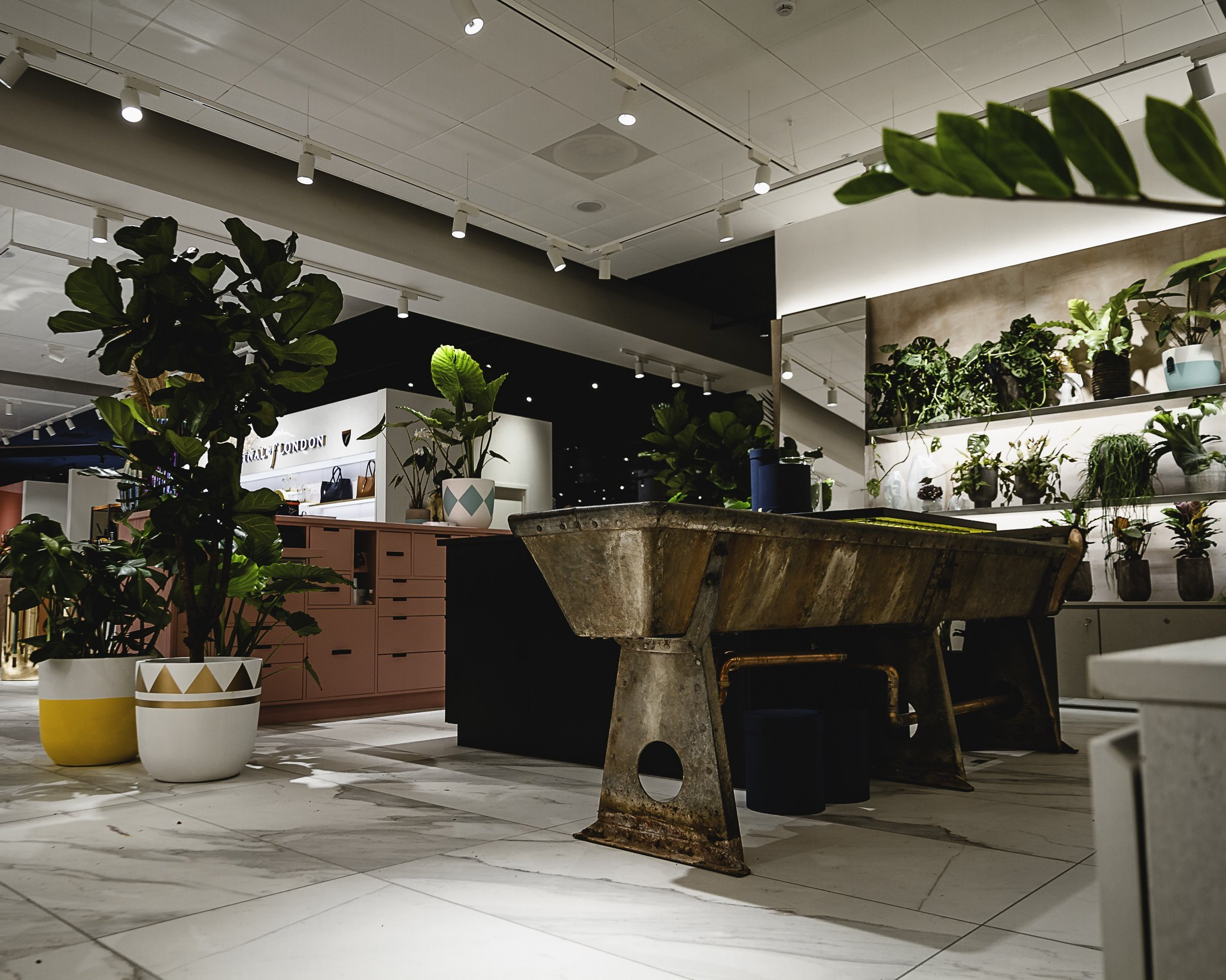 Side view of a interior shop fit out in Selfridges store with a vintage style horse trough with fashionable rusting effect