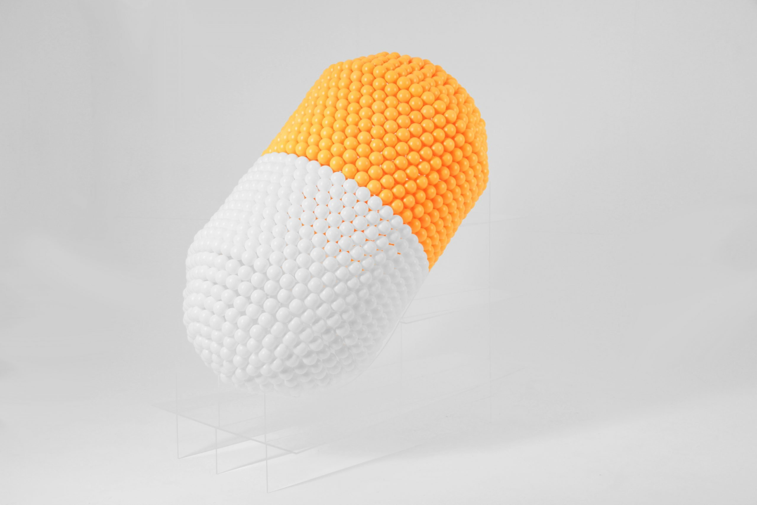 Sculpture of a pill which is half orange and half white. The structure is made from ping pong balls. Designed and created by design studio Lazerian.