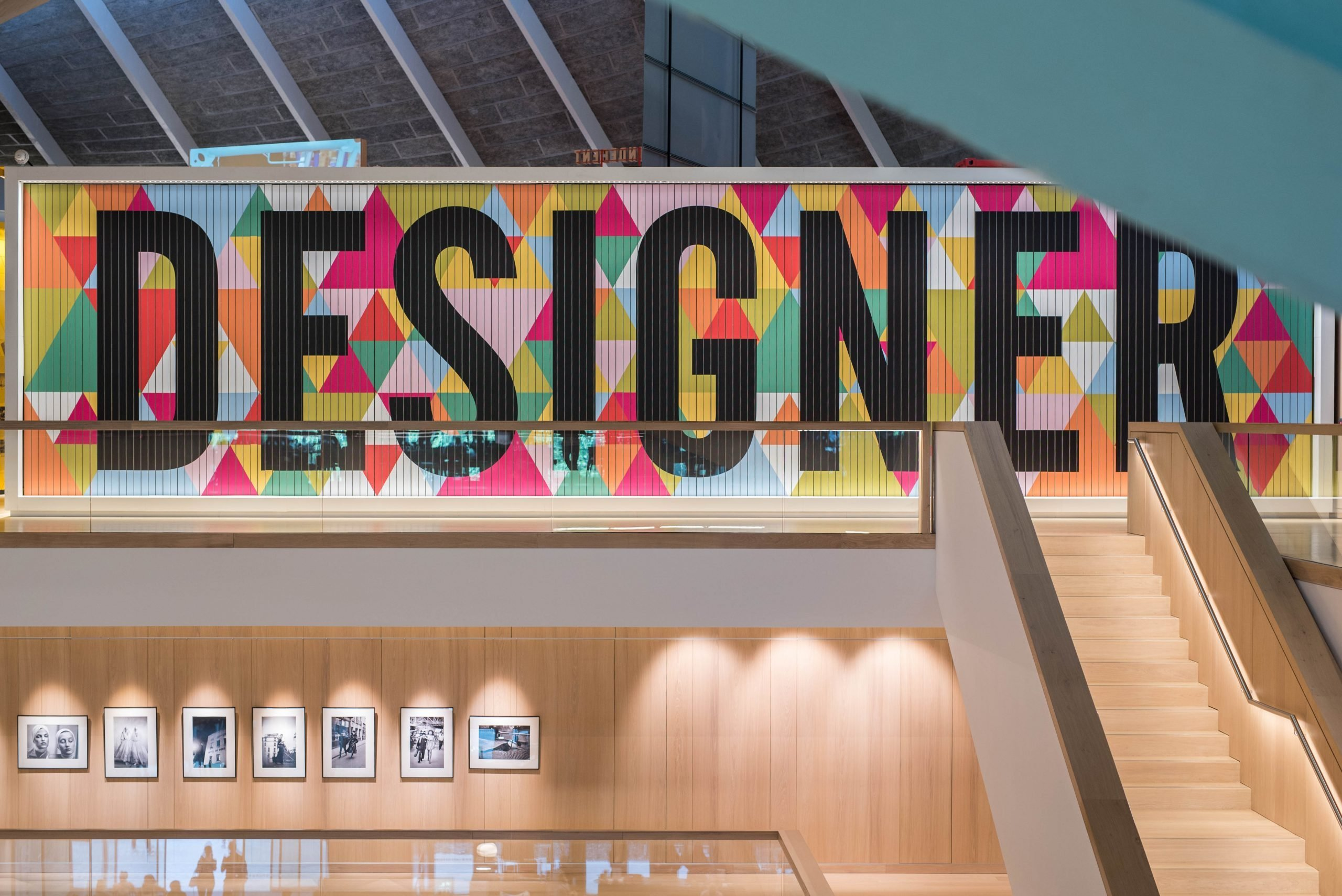 Showing a escalator on the right hand side with the main focus being the wall at the top of the stairs. Large black block letters 'Designer' are in front of a colourful pattern consisting of small triangles. Located in London at the Design Museum