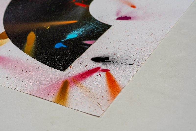 Left corner view of Set 3 of a limited edition set of art prints inspired by the corona virus and lockdown experiences. It includes a black rainbow type shape and a white baclground with different coloured specks of spray paint around. Designed and created by Liam Hopkins of Lazerian