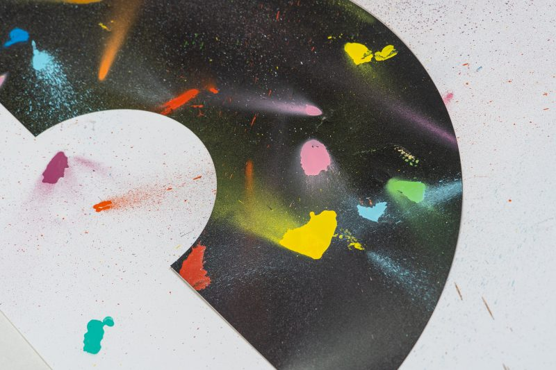 right hand view of Set 3 of a limited edition set of art prints inspired by the corona virus and lockdown experiences. It includes a black rainbow type shape and a white baclground with different coloured specks of spray paint around. Designed and created by Liam Hopkins of Lazerian