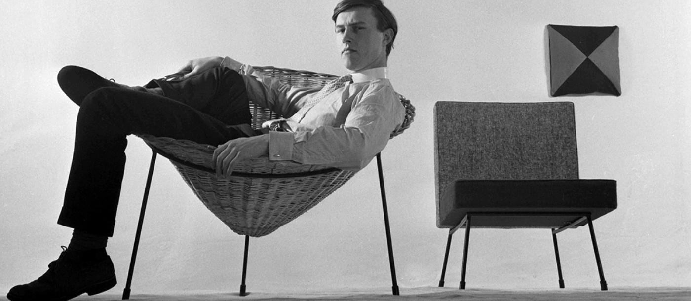 Black and white image of sir terence conran sitting in a chair in a laid back style