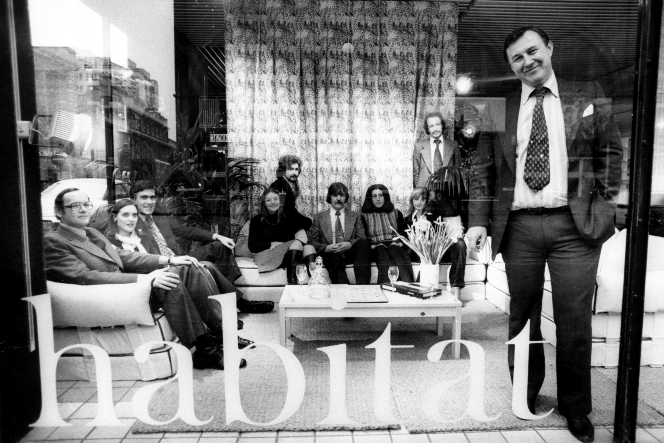 Black and white vintage photo advertising design store Habitat when it originally opened. With a man in a suit stood smiling out of a large shop front window whilst a team of staff are sat on a large sofa behind him.