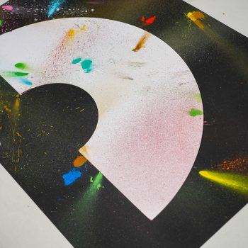 A art print inspired by the coronavirus experience. A black background with a white crescent rainbow shape in the centre. Splattered randomly with different coloured spray paints such as blues, reds, pinks, yellows and greens. Designed and created by artist and designer Liam Hopkins of design studio Lazerian. This photo shows an angled view of the painting.