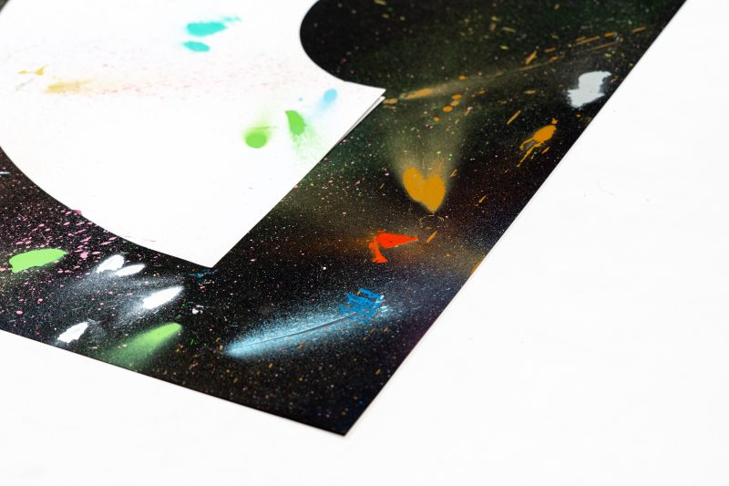 A art print inspired by the coronavirus experience. A black background with a white crescent rainbow shape in the centre. Splattered randomly with different coloured spray paints such as blues, reds, pinks, yellows and greens. Designed and created by artist and designer Liam Hopkins of design studio Lazerian.. This image shows the left hand corner of the painting.
