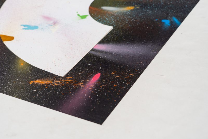 A art print inspired by the coronavirus experience. A black background with a white crescent rainbow shape in the centre. Splattered randomly with different coloured spray paints such as blues, reds, pinks, yellows and greens. Designed and created by artist and designer Liam Hopkins of design studio Lazerian. Left hand view of the corner of the print showing off a fuchsia pink streak.