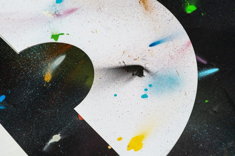 A art print inspired by the coronavirus experience. A black background with a white crescent rainbow shape in the centre. Splattered randomly with different coloured spray paints such as blues, reds, pinks, yellows and greens. Designed and created by artist and designer Liam Hopkins of design studio Lazerian. A right corner view.