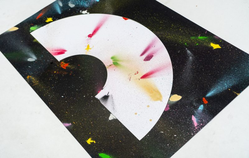 A art print inspired by the coronavirus experience. A black background with a white crescent rainbow shape in the centre. Splattered randomly with different coloured spray paints such as blues, reds, pinks, yellows and greens. Designed and created by artist and designer Liam Hopkins of design studio Lazerian. A angled shot of the painting.